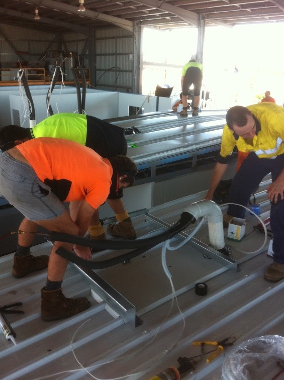 Johnny Cool Darwin team fitting off the Electrical wiring and cabling for roof mounted condensors